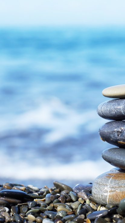 Stack of round stones on the seashore Complementary Therapist