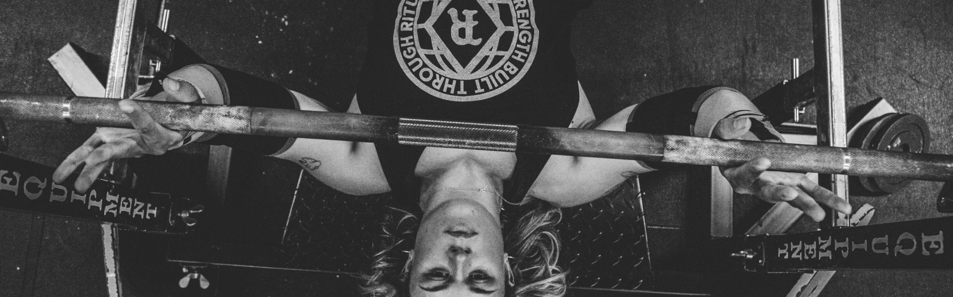 black and white image lifting weight on bench, insurance for fitness
