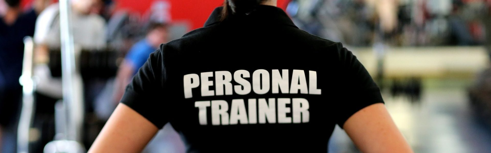 insurance, personal trainer in t-shirt in a gym